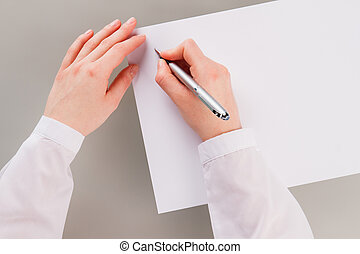 Female hand holding pen and writing on blank paper.