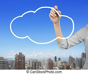 Female hand holding pen drawing white cloud in sky