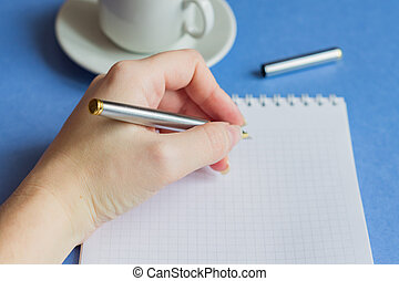 female hand holding pen, with a blank notes and cup of coffee on blue background, selective focus
