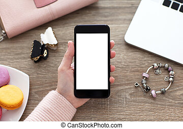 female hand holding phone isolated screen on table with jewelry