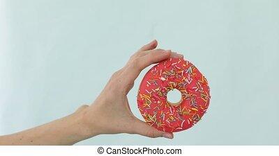 Female hand holding pink donut on blue background - Female...