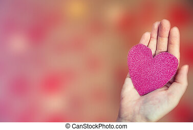 Female hand holding pink glitter heart on romantic blurred bokeh background, copy space or space for text, Valentine's day or romantic background