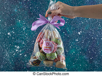 Female hand holding plastic bag of cookies