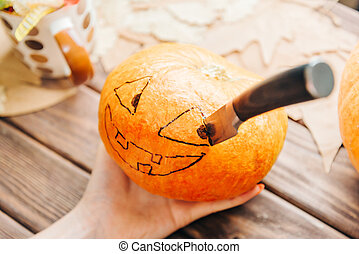 Female hand holding pumpkin with drawing Jack-o-lantern sketch and knife.