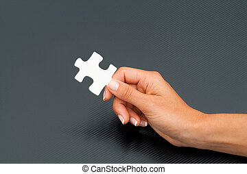 Female hand holding puzzle piece.