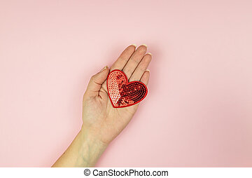 Female hand holding red sequin heart on pink background. Creative minimal layout with copy space