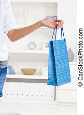 Female hand holding shopping bag