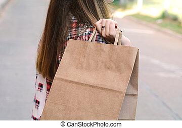 Female hand holding shopping bag outdoors.