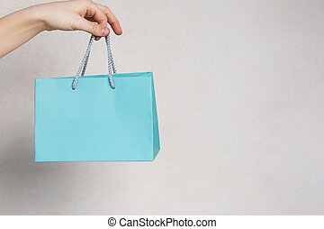 Female hand holding small package with a gift over a grey background. Empty space
