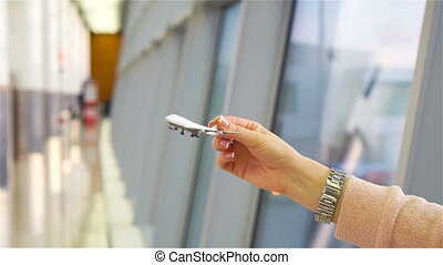 Female hand holding toy airplane, copy space for text. Passenger with small model airplane at the airport. SLOW MOTION
