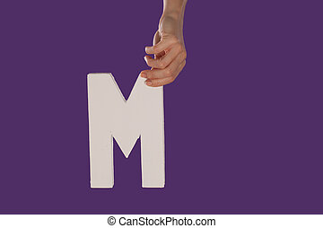 Female hand holding up the letter M from top