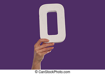 Female hand holding up the letter O from the bottom