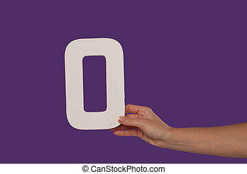 Female hand holding up the letter O from the right