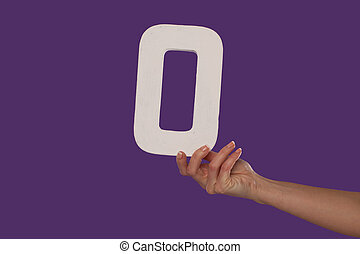 Female hand holding up the number 0 from the right