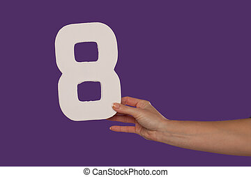 Female hand holding up the number 8 from the right