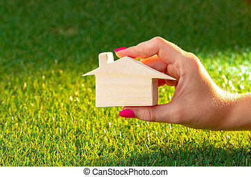Female hand holding wooden house model above the grass