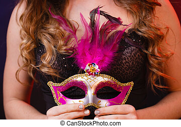 Female hand holds carnival mask closeup