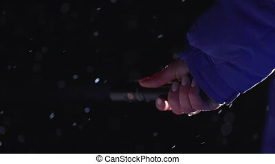 Female hand holds flashlight and shines at night, looking for something. Winter, snowfall, blizzard, cold temperature. High quality 4k footage