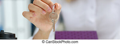 Female hand holds the key to the lock in the hand