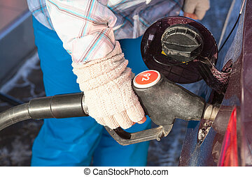 Female hand in mittens refueling vehicle in winter