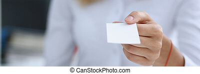 Female hand in suit give blank calling card to male visitor