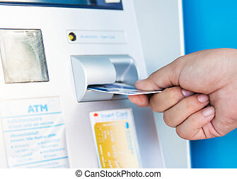 female hand inserting ATM card into bank machine to withdraw money