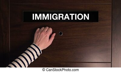 Female hand knocking at immigration service door, refuge...