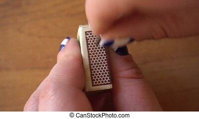 female hand lighting a match on a matchbox