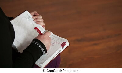 Female hand making notes in a notebook