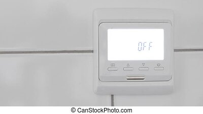 Female hand off a temperature sensor on a white wall