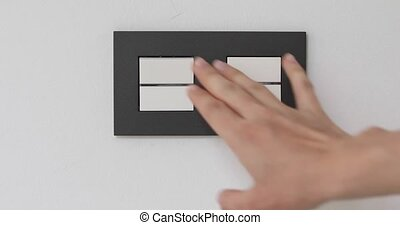 Female hand on light double-switch - Female hand presses...