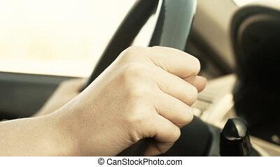 Female hand on steering wheel. Very fast driving.