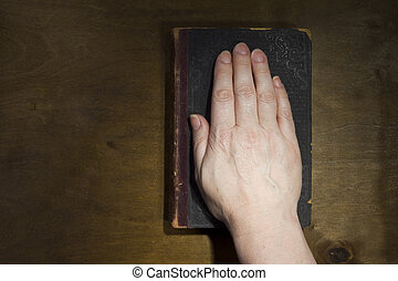 Female hand on the Bible