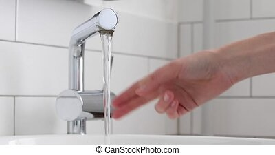 Female hand open mixer with water in bathroom - Female hand...
