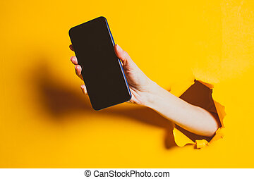 Female hand out of the hole in the paper wall, holding smartphone with a black screen.