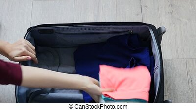 female hand packing suitcase for trip, top view