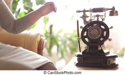Female hand picks up the phone.