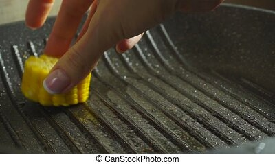 Female hand placing corn cob pieces on hot grill pan clip