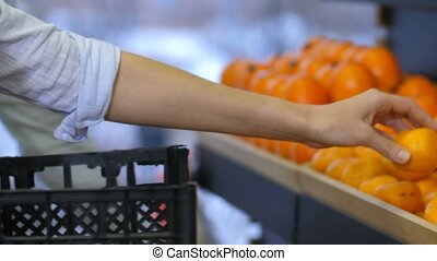 Female hand placing fresh tangerines on store shelf -...