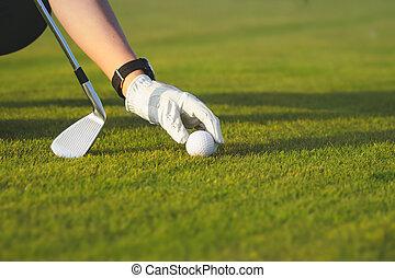 female hand placing golf ball on tee