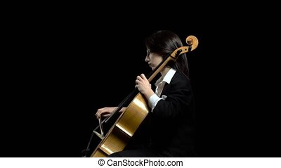 Female hand plays with a bow on a cello in dark studio ....