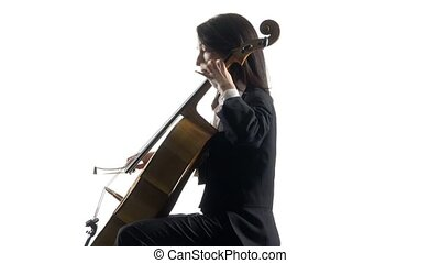 Female hand plays with a bow on a cello in white studio ....