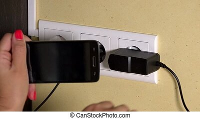 Female hand plug smart phone to wall charger and hold in...