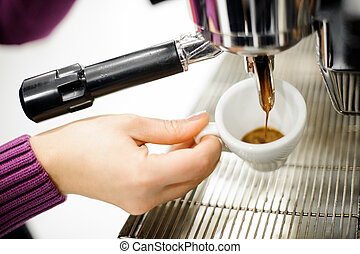 Female hand pouring a fresh and aromatic coffee from a coffee machine