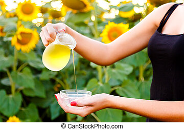 Female hand pours sunflower oil from a jug into a bowl.