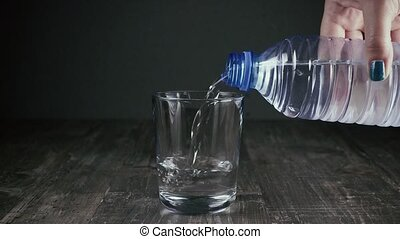 Female hand pours water into a glass