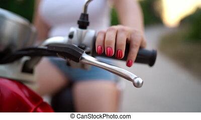 Female hand presses brake on red vintage retro scooter....