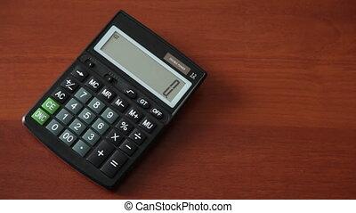 female hand presses the button on calculator