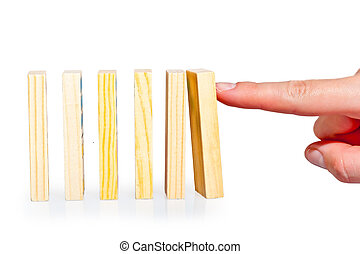 female hand pushing a row of dominoes lined up