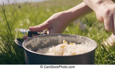 Female hand puts hot porridge after cooking in camping close up